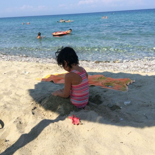 Lastborn enjoys a final dig in the sand, Greece