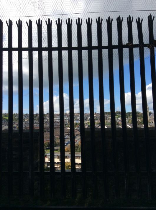 View of Bogside through fence.  Behind, is a row of prominent Protestant buildings.  Catholics would often lob missiles over the walls at this point.